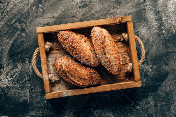 top view of arranged loafs of bread in wooden box on dark tabletop with flour Stock photo © LightFieldStudios