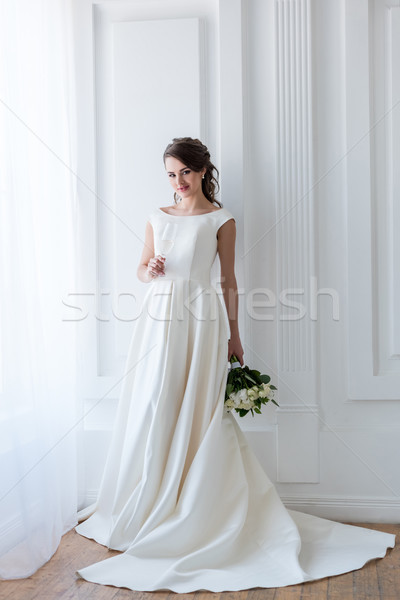 beautiful bride in traditional dress with wedding bouquet and glass of champagne Stock photo © LightFieldStudios