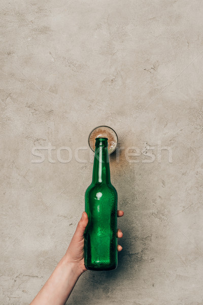 Close-up view of hand pouring drink in glass on light background Stock photo © LightFieldStudios