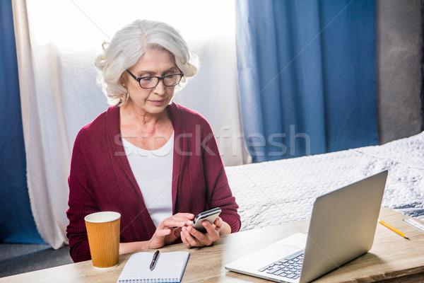 Vrouw smartphone aantrekkelijk senior bril vergadering Stockfoto © LightFieldStudios
