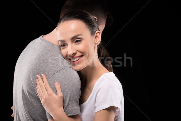 portrait of smiling woman bonding to man and looking away on black Stock photo © LightFieldStudios
