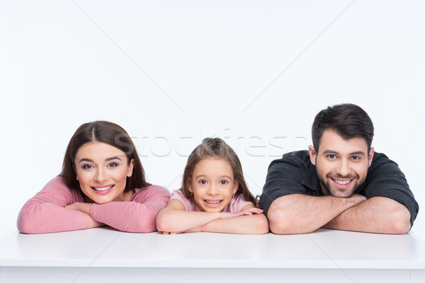 Happy family with one child leaning on white table and smiling Stock photo © LightFieldStudios