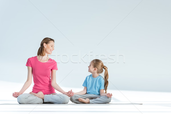 Smiling sporty mother and daughter practicing lotus position with gyan mudra asana on white Stock photo © LightFieldStudios