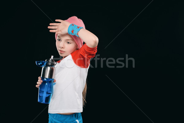tired girl in sportswear holding sport bottle isolated on black. athletics children concept Stock photo © LightFieldStudios