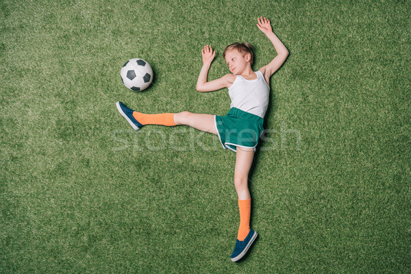 top view of little boy pretending playing soccer on grass, athletics children concept Stock photo © LightFieldStudios