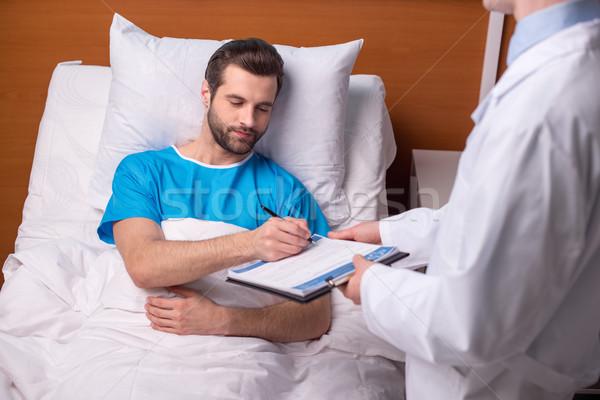 пациент подписания медицинской документа больным молодым человеком Сток-фото © LightFieldStudios