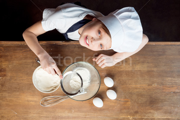 Stock photo: overhead view of boy making dough for cookies on wooden table