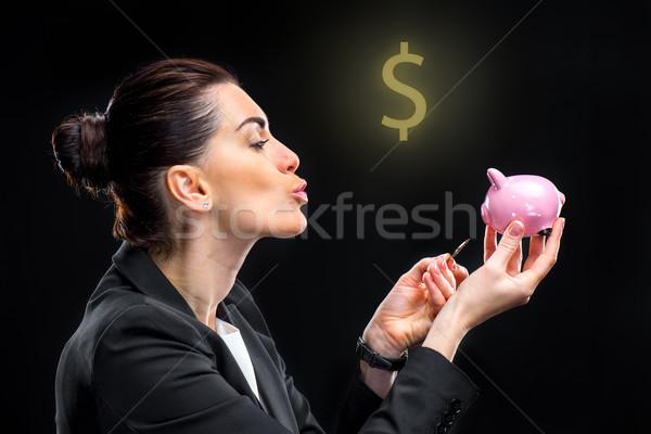 businesswoman feeding piggy bank  Stock photo © LightFieldStudios