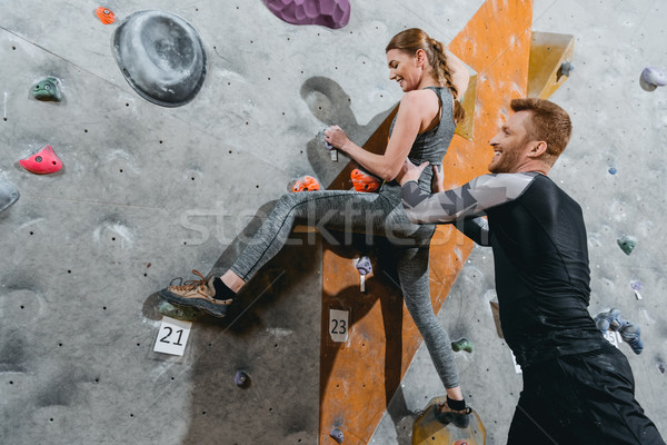young woman climbing wall with grips Stock photo © LightFieldStudios