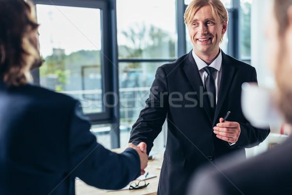 Empresarios apretón de manos tiro profesional oficina Foto stock © LightFieldStudios