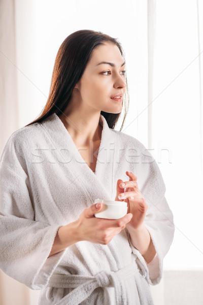 Stock photo: woman applying face cream