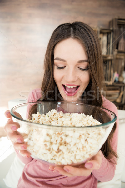 Excited young brunette woman holding glass bowl with popcorn Stock photo © LightFieldStudios