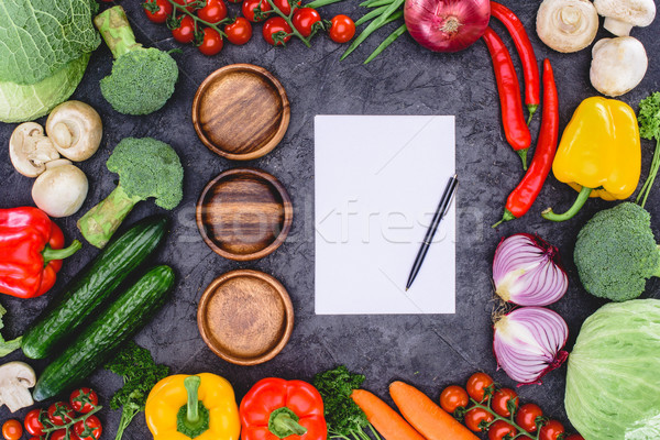 top view of three empty wooden plates, blank paper with pen and fresh assorted vegetables on black Stock photo © LightFieldStudios