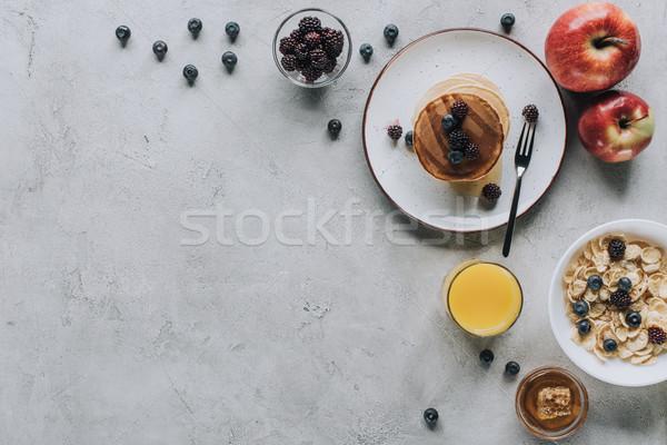 top view of tasty healthy breakfast with pancakes, fruits, honey and muesli on grey   Stock photo © LightFieldStudios