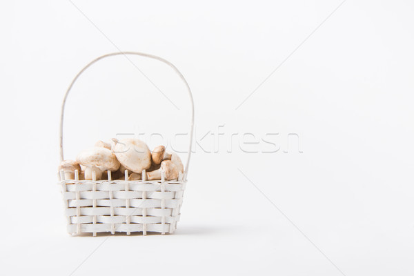 heap of champignon mushrooms laying in wicker basket on white background  Stock photo © LightFieldStudios