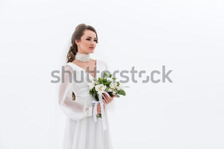 Stock photo: attractive bride in traditional dress holding wedding bouquet, isolated on white