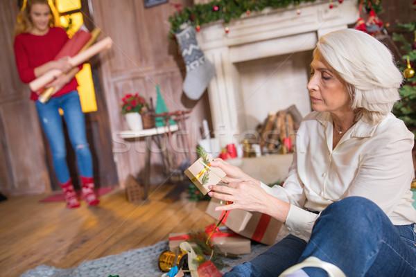 Woman wrapping christmas presents Stock photo © LightFieldStudios