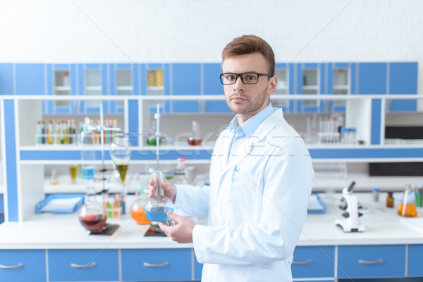 Young man scientist in eyeglasses holding flask with reagent and looking at camera Stock photo © LightFieldStudios
