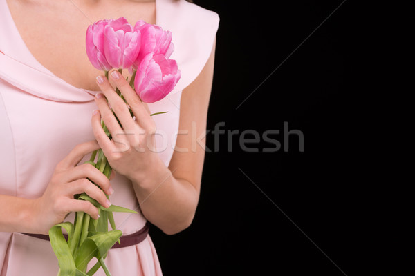 Close-up partial view of woman in dress holding pink tulips on black, international womens day conce Stock photo © LightFieldStudios