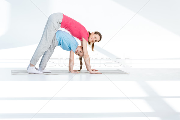 Happy mother and daughter exercising on yoga mat and smiling at camera Stock photo © LightFieldStudios