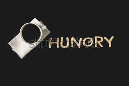 top view of word hungry made from cookie dough and coffee cup isolated on black Stock photo © LightFieldStudios