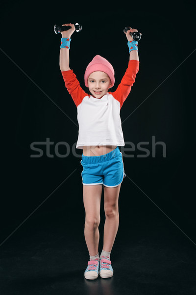 Stock photo: girl training with dumbbells isolated on black. active kids isolated concept