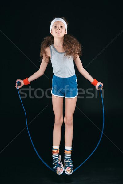 Ragazza abbigliamento sportivo jumping corda isolato nero Foto d'archivio © LightFieldStudios