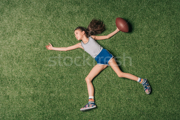 top view of little sportive girl throwing rugby ball on grass, athletics children concept Stock photo © LightFieldStudios