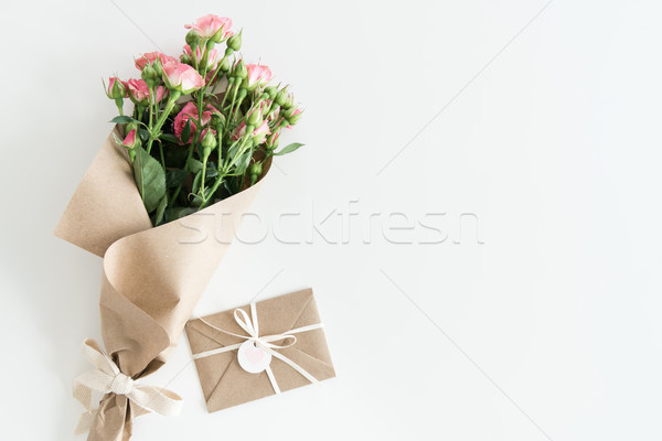 pink roses bouquet in kraft paper and envelope isolated on white with copy space, wedding cards flow Stock photo © LightFieldStudios