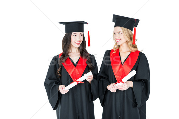 Two beautiful young students in academic caps holding diplomas and smiling each other Stock photo © LightFieldStudios