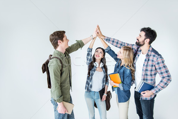 four young students in casual clothes holding books and giving highfive on white Stock photo © LightFieldStudios
