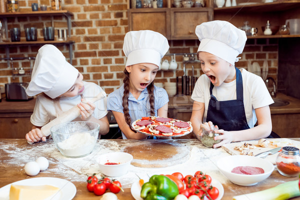 kids in chef hats making pizza together Stock photo © LightFieldStudios