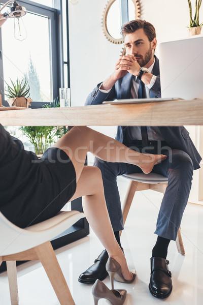 Woman flirting with man under table Stock photo © LightFieldStudios