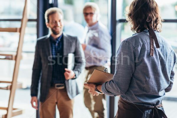 Cameriere saluto imprenditori cafe vista posteriore di mezza età Foto d'archivio © LightFieldStudios