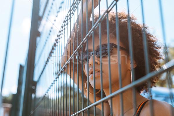 Kobieta za ogrodzenie młodych okulary stwarzające Zdjęcia stock © LightFieldStudios