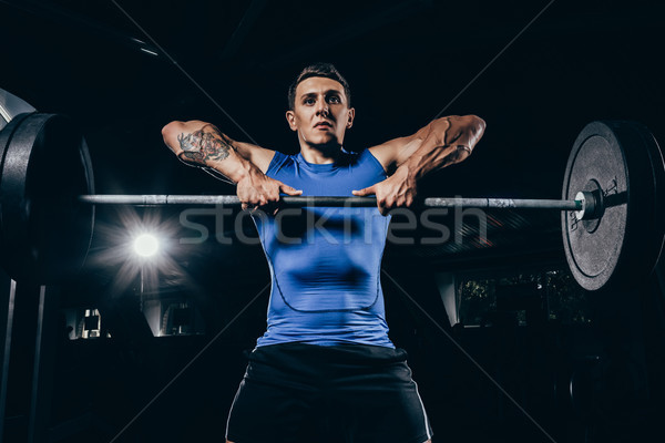 athletic sportsman lifting barbell Stock photo © LightFieldStudios