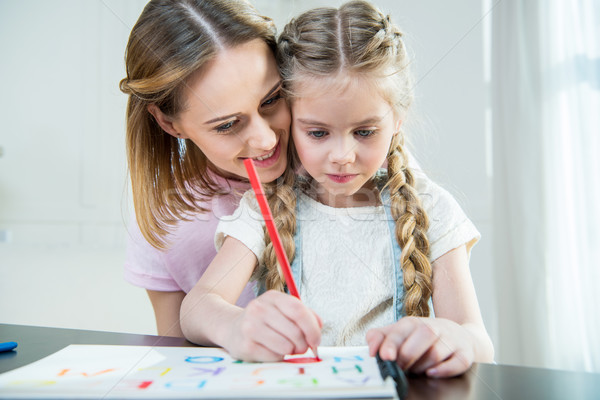Happy mother and focused daughter drawing colorful letters at home Stock photo © LightFieldStudios