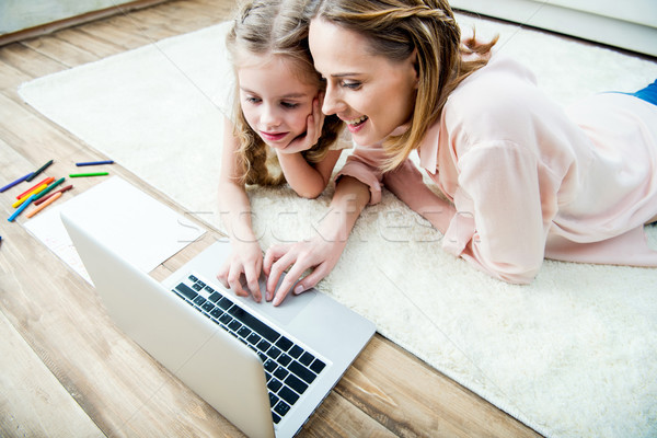 side view of smiling mother and concentrated daughter using laptop Stock photo © LightFieldStudios