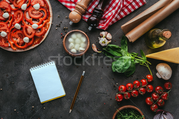 top view of uncooked pizza with notebook on concrete table Stock photo © LightFieldStudios