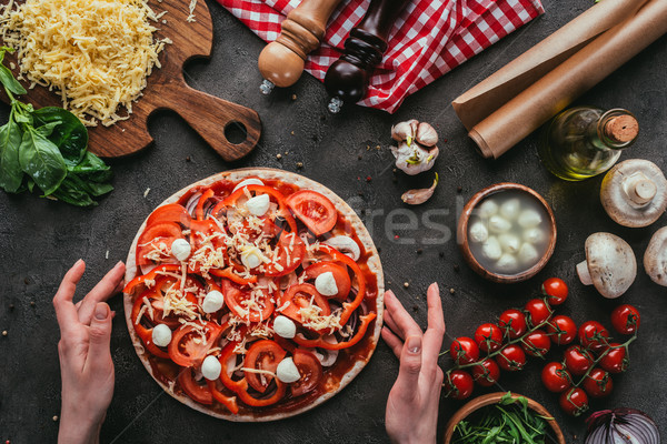 cropped shot of woman holding unbaked pizza on concrete table Stock photo © LightFieldStudios