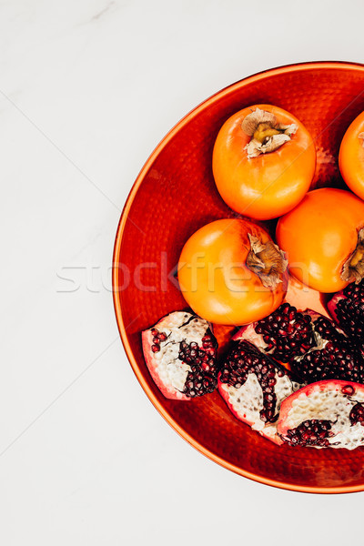 top view of persimmons and pomegranates on red plate isolated on white Stock photo © LightFieldStudios