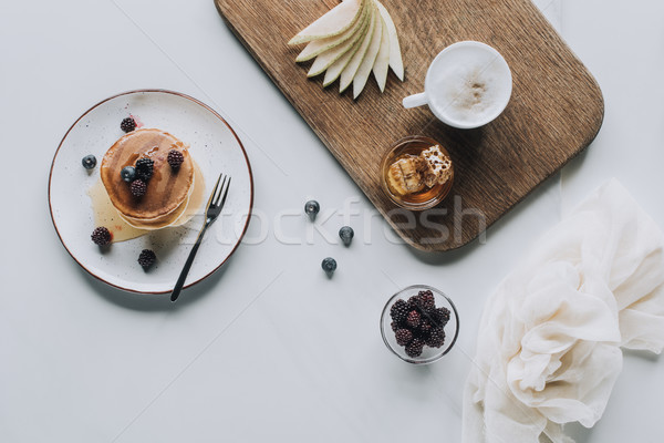 top view of tasty healthy pancakes with berries and cup of cappuccino on grey  Stock photo © LightFieldStudios
