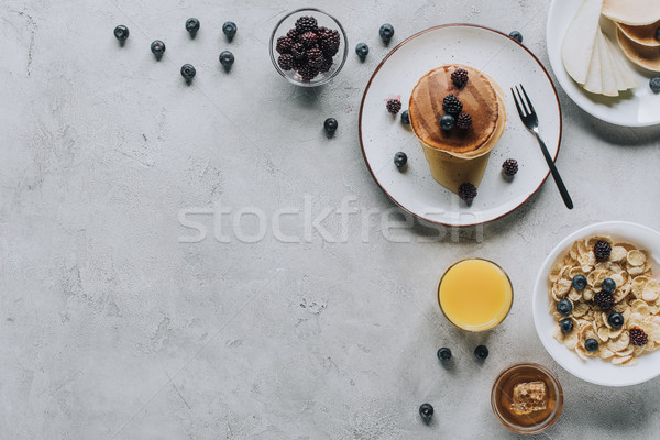 top view of delicious homemade breakfast with pancakes, fruits, honey and muesli on grey     Stock photo © LightFieldStudios