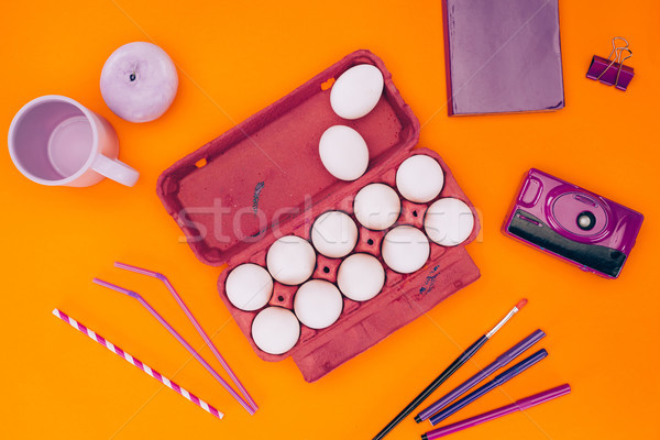 elevated view of chicken eggs in egg tray and felt tip pens for easter painting isolated on orange Stock photo © LightFieldStudios