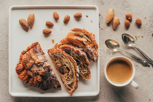 top view of cup of coffee and sweet pastry with almonds on plate on light tabletop Stock photo © LightFieldStudios