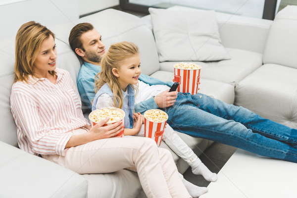 smiling family with popcorn watching film together at home Stock photo © LightFieldStudios