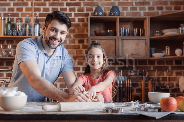 'Happy father and daughter kneading dough and smiling at camera  Stock photo © LightFieldStudios