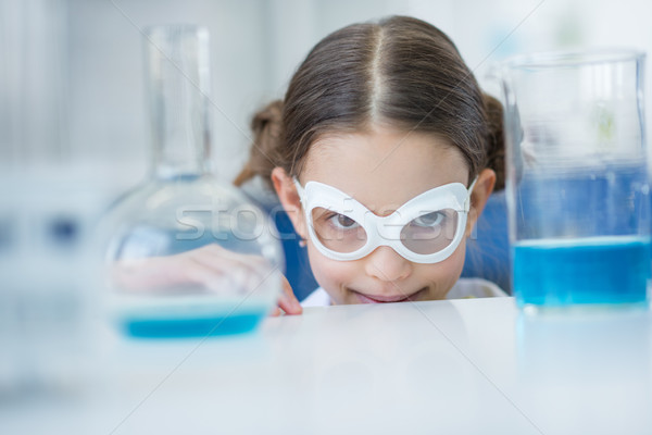 Stock photo: Little girl scientist in protective glasses smiling at camera in lab