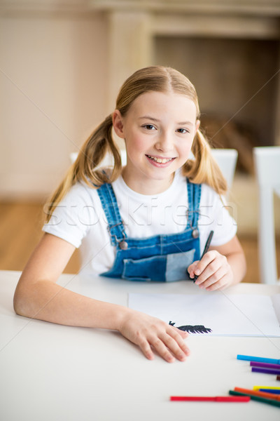Adorable little girl drawing at table and smiling at camera Stock photo © LightFieldStudios