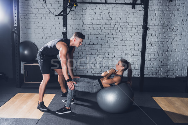 trainer helping woman work out Stock photo © LightFieldStudios